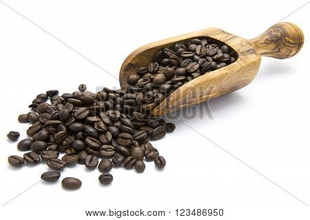 Roasted coffee beans in wooden scoop on white isolated background