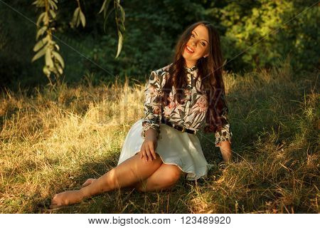 Happy girl sits on grass and poses in beams of sunset sun