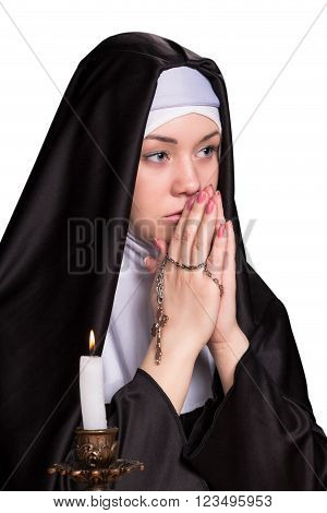 Portrait of nun with her hands folded together and holding a cross with candle burning near isolated on white background