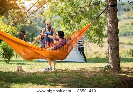 Couple in love toasting with beer in hammock with friend