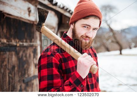 Smiling bearded man in checkered shirt and hat holding axe