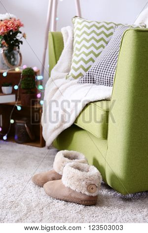 Slippers near armchair in interior of living room
