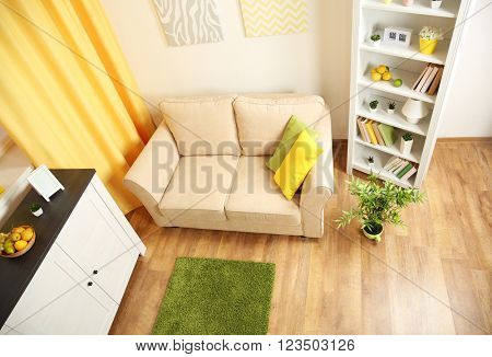 Modern living room interior with beige sofa, white furniture and bright decor