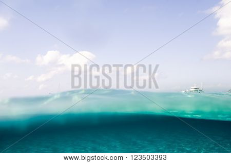 A yatch on the sea surface with the sky and the sea bottom in the Mediterranean Sea