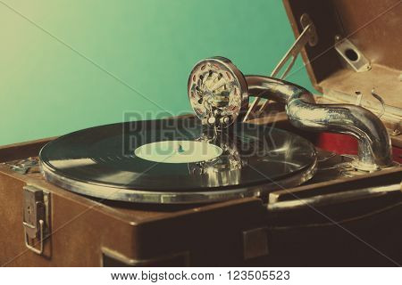 Gramophone with vinyl record on table on wall background