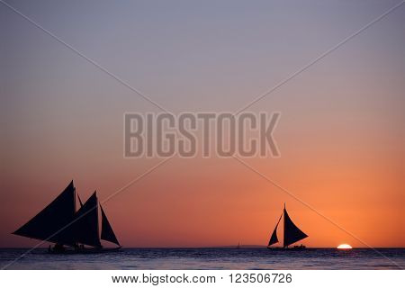 Yachts sailing in tropical sea at sunset