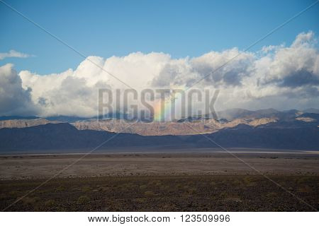 Rainbow in storm clouds over Cottonwood Mountains in Death Valley National Park.