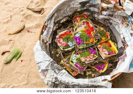 SANUR, BALI - MAR 18, 2016: Donations sacrifice during Melasti Ritual. Ceremony is held on the edge of the beach with the aim to purify oneself of all the bad things in the past and throw it to ocean.