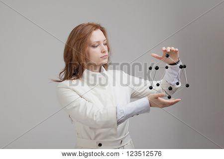 Woman scientist holding model of molecule or crystal lattice.