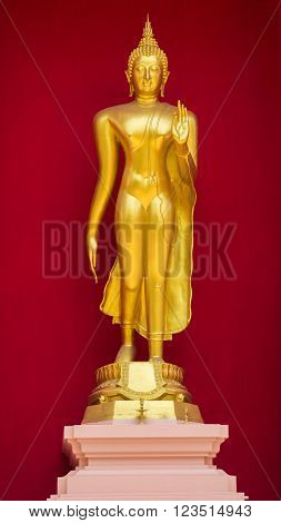 Golden Buddha in standing position on red background.