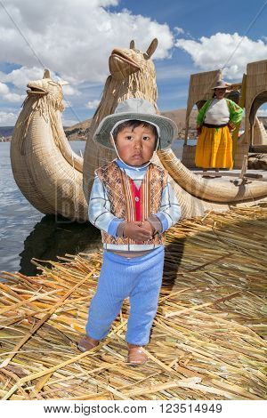 Puno, Peru - Circa June 2015: Small Boy In Traditional Clothes And Canoe Boat At Uros Floating Islan