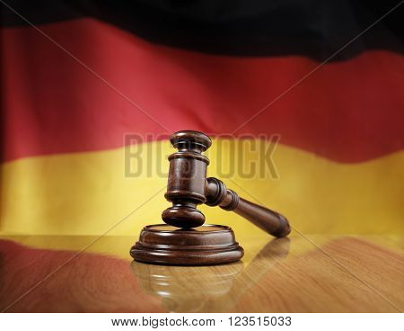 Mahogany wooden gavel on glossy wooden table, flag of Germany in the background.