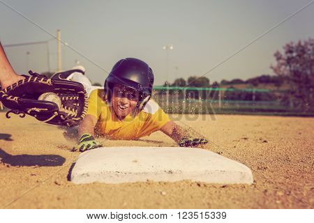 Youth Baseball playing sliding back to base. Focus on glove and ball