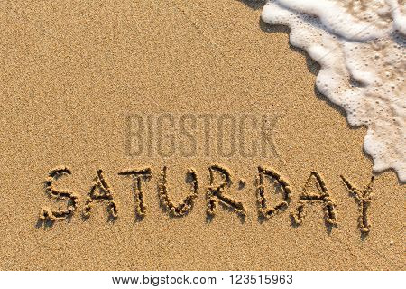 Week series - SATURDAY - written on a sandy beach with the soft wave at sunny day.