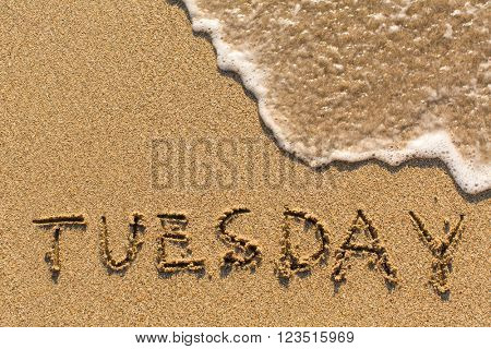 Week series - TUESDAY - written on a sandy beach with the soft wave at sunny day.
