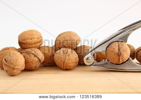English or Persian walnuts and metal nutcracker on a wooden background ** Note: Soft Focus at 100%, best at smaller sizes