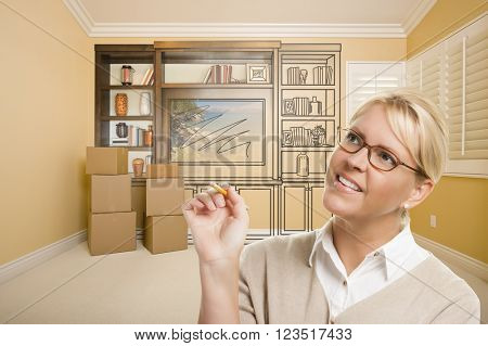 Female Holding Pencil In Room With Moving Boxes and Drawing of Entertainment Unit On Wall.