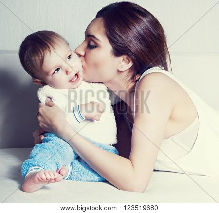 young mother kissing her one year old baby at home