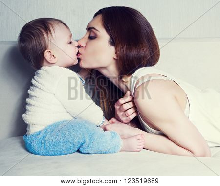 mother kissing her one year old baby at home