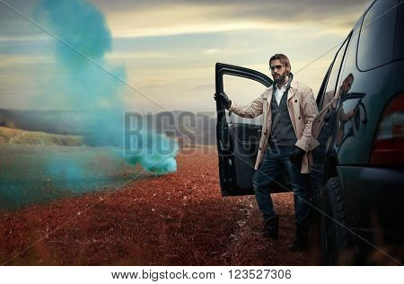 Handsome fashion man near the car