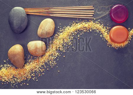 Vintage toned stones on slate background with incense sticks and soaps, spa and wellness background.