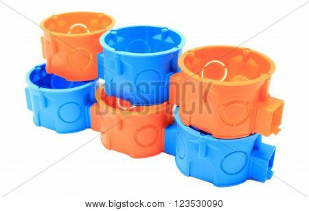 Stack of orange and blue plastic electrical boxes on white background, junction boxes, accessories for engineering jobs