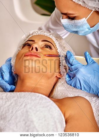 Woman middle-aged in spa salon with beautician. Beauty female giving injections. Aesthetic medicine.