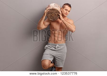 Handsome muscular guy carrying a huge log on his shoulder and looking at the camera