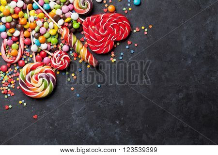 Colorful candies and lollypops on dark stone background. Top view with copy space