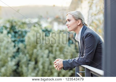 A young businesswoman leaning against the railing of her office balcony