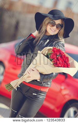 The young woman, the blonde with a thick long hair, in sun glasses, a black leather jacket and black leather trousers, in a black hat with big fields, with a big bouquet of scarlet roses poses near the red car loaded by gift boxes ** Note: Visible grain