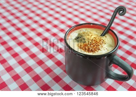 Black coffee with rich crema in a black ceramic mug on a background of red and white checkered cloth
