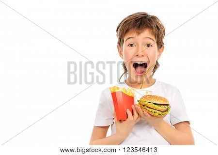 Emotional nine year old boy holds french fries, burger and soda and shouting. Fast food. Concept of healthy and unhealthy food. Isolated over white.