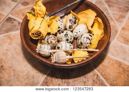 quail eggs with yellow flower are on the brown tile floor,cook on the kitchen,healthy food,Easter