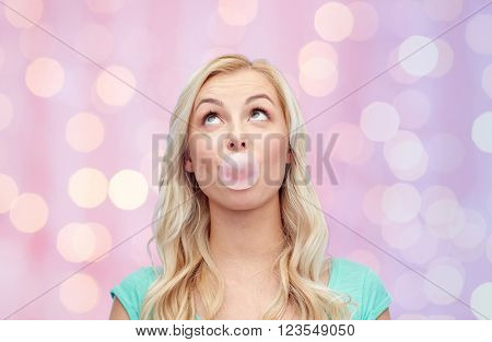 emotions, expressions and people concept - happy young woman or teenage girl chewing gum over pink holidays lights background