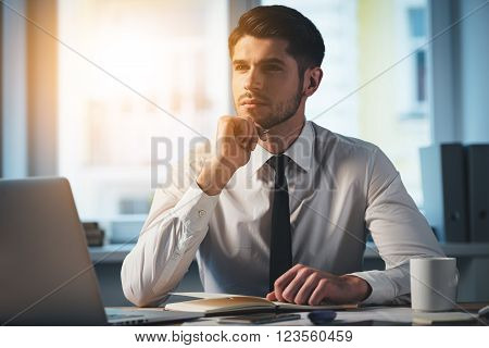 Searching for the right solution. Pensive young handsome man keeping hand on chin and looking away while sitting at his working place