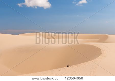Alone man in desert. The White Dunes (bau sen bau trang)- landmark near Mui Ne Binh Thuan Vietnam.