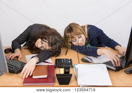 Two Young Office Employee Asleep On Desk For Computers