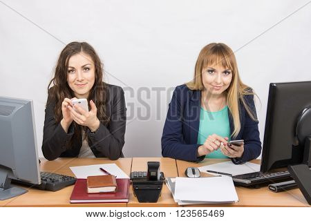 Two Office Employee Engaged In Personal Business In Mobile Phones At His Desk