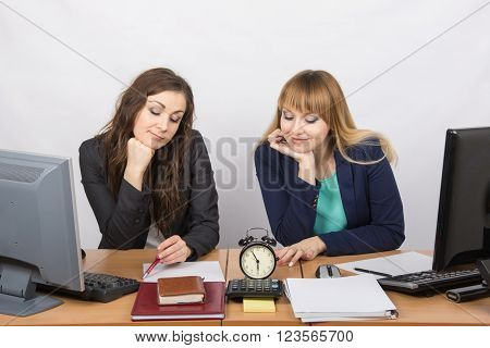 Two Employee In The Office Looking At The Clock And Waiting For The End Of The Working Time