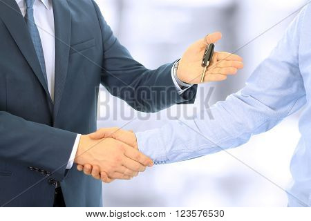Car salesman handing over the keys for a new car to a young businessman . Handshake between two business people. Focus on a key