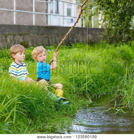 Two happy kid boys fishing on a river with selfmade fishing rod  on sunny summer day. Happy children having fun. Active leisure for children outdoors.