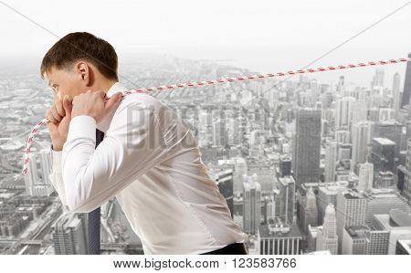 Businessman pulling a rope on city background