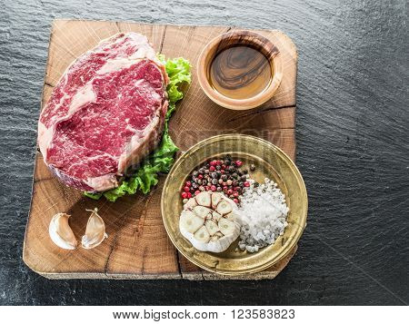 Steak Ribeye with spices on the old wooden tray.