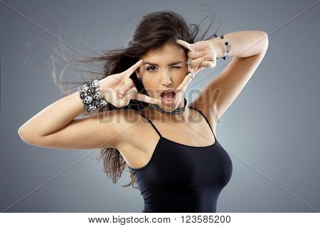 Beautiful young woman posing showing rock on hand gesture with both hands and winking.