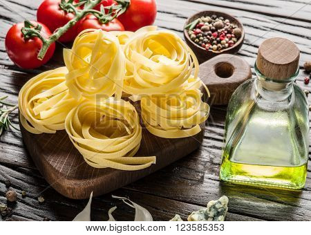 Pasta ingredients. Cherry-tomatoes and spaghetti pasta on the wooden table.