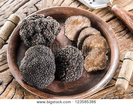 Black truffles on the plate on the old wooden table.