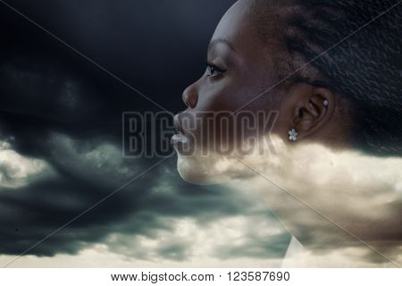 Double exposure portrait of beautiful woman. Beauty portrait of young african woman in profile with storm cloudy sky