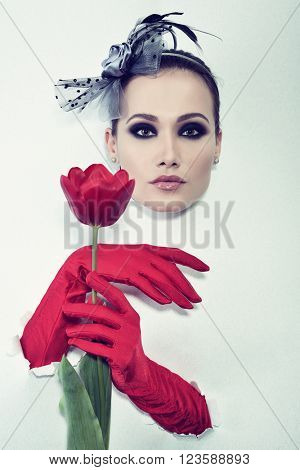 Retro fashion portrait of young woman with one red glove and tulip, image toned.
