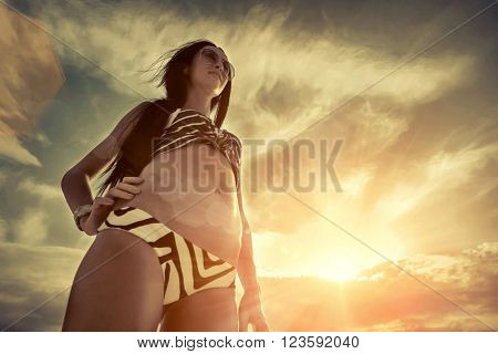Woman stay on the beach under sky with sunlight.
